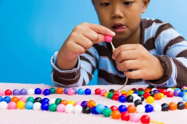 Un garçon est occupé à enfiler des perles sur une ficelle.