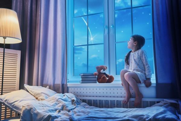Une fille regarde une étoile filante par la fenêtre
