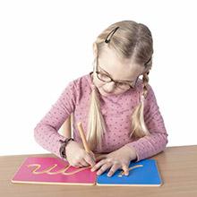 Une fille trace les lettres creusées Montessori - de l\'écriture vers la lecture