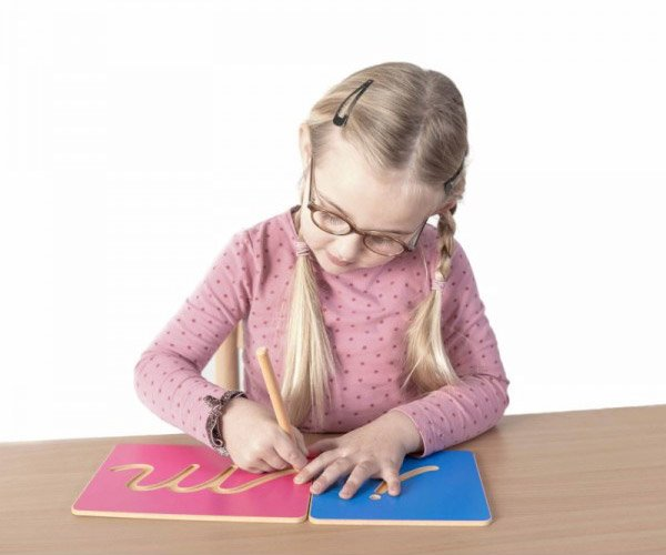 Une fille trace les lettres creusées Montessori - de l'écriture vers la lecture