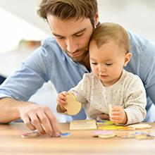 Un père aide son enfant à faire un puzzle